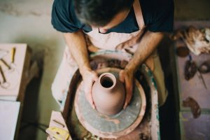 Garyling Ceramic Medium top down shot of man spinning a pottery vase while wearing a apron